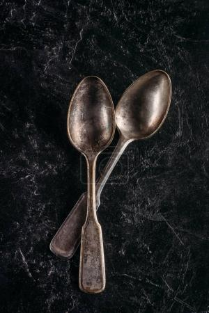 Vintage metal spoons on dark background