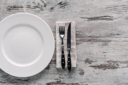 Photo for White plate and fork with knife on napkin on wooden table - Royalty Free Image