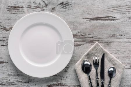 Photo for White plate and cutlery on napkin on wooden background - Royalty Free Image