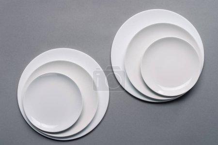 glänzend weiße Keramikteller auf grauem Hintergrund