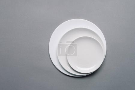 White plates of different sizes on grey background