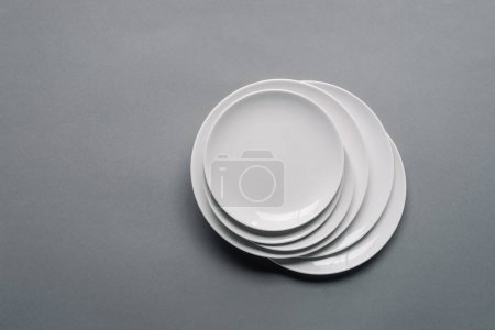 Stack of white porcelain plates on grey background