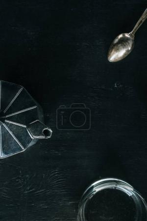 flat lay with coffee maker, empty glass and spoon on black tabletop