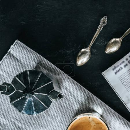 flat lay with coffee maker, spoons and glass of cold iced coffee on black tabletop