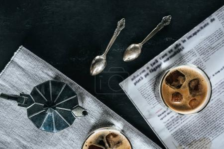 flat lay with coffee maker, spoons, newspaper and glasses of cold brewed coffee on black tabletop