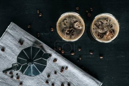 flat lay with coffee maker and glasses of cold brewed coffee on black tabletop