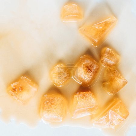 top view of brown ice cubes made of coffee on white tabletop