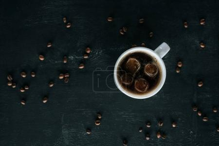 top view of mug of cold iced coffee on dark tabletop with roasted coffee beans around