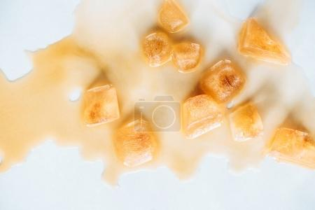Photo for Top view of brown ice cubes made of coffee on white tabletop - Royalty Free Image