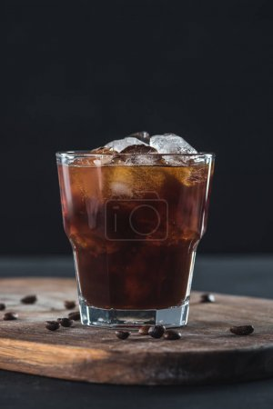 close up view of glass of cold brewed coffee with roasted coffee beans on wooden cutting board on dark backdrop