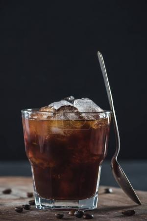 close up view of glass of cold brewed coffee with spoon on wooden cutting board on dark backdrop