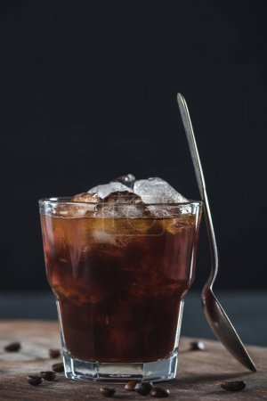 Photo for Close up view of glass of cold brewed coffee with spoon on wooden cutting board on dark backdrop - Royalty Free Image