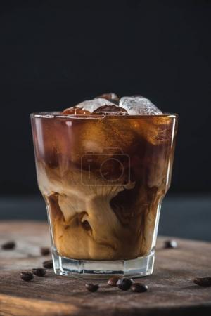 Photo for Close up view of glass of cold brewed coffee with roasted coffee beans on wooden cutting board on dark backdrop - Royalty Free Image