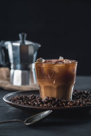 selective focus of glass of cold iced coffee on plate with roasted beans and coffee maker on tabletop on dark backdrop