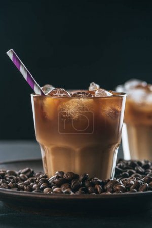 selective focus of glass of cold iced coffee with straw on plate with roasted coffee beans on tabletop on dark backdrop