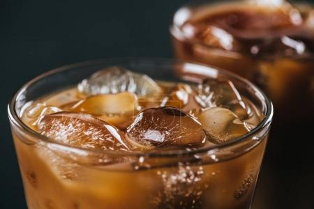 close up view of ice cubes in cold brewed coffee in glass on dark background