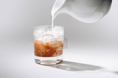 close up view of pouring milk into glass of iced coffee process on white tabletop