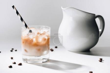 close up view of jag of milk and glass of cold brewed coffee with straw on white tabletop