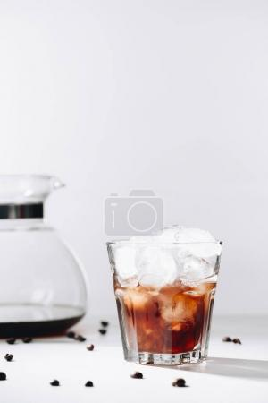 close up view of glass of cold brewed coffee, coffee maker and roasted coffee beans on grey background