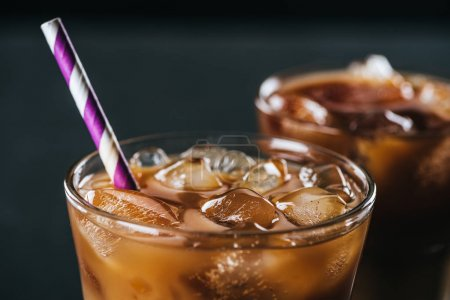 Photo for Selective focus of glass of cold iced coffee with straw on dark background - Royalty Free Image