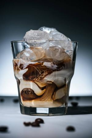 close up view of cold brewed coffee with ice cubes and roasted coffee beans on tabletop in glass on dark backdrop
