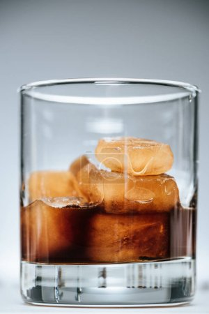 close up view of cold iced coffee with ice cubes in glass on grey background