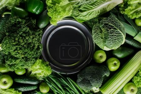 top view of black plate between green vegetables, healthy eating concept