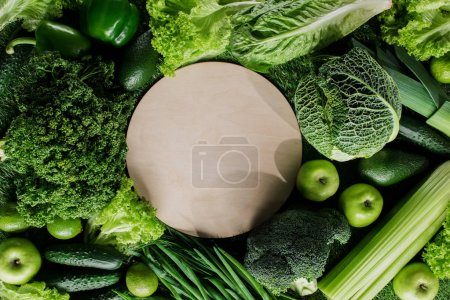 Photo for Top view of round wooden board between green vegetables, healthy eating concept - Royalty Free Image