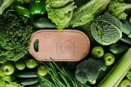 top view of cutting board between green vegetables and fruits, healthy eating concept