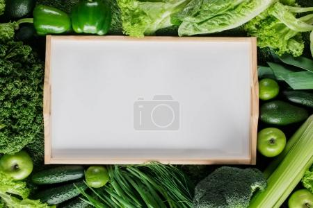 elevated view of blank tray between green vegetables, healthy eating concept