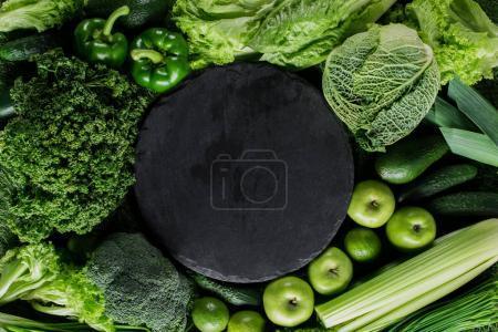 Foto de Vista superior de la tabla de cortar negra entre verduras, concepto de alimentación saludable - Imagen libre de derechos