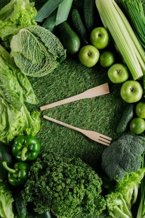 Photo for Top view of wooden spatula and fork between green vegetables, healthy eating concept - Royalty Free Image