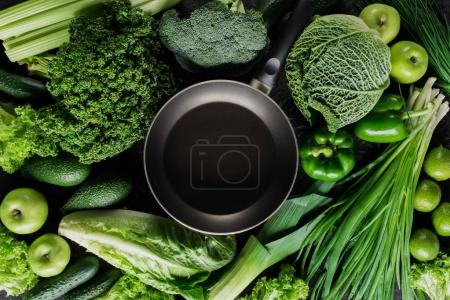 Photo for Top view of frying pan between green vegetables, healthy eating concept - Royalty Free Image