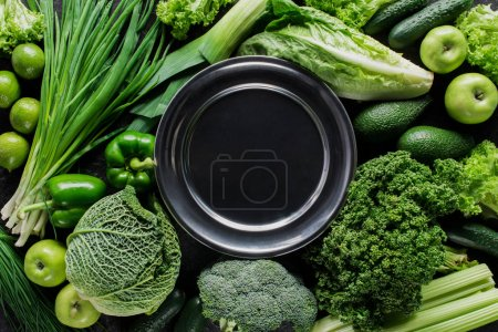 Photo for Top view of black plate between green vegetables, healthy eating concept - Royalty Free Image