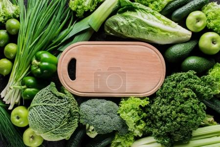 Photo for Top view of cutting board between green vegetables, healthy eating concept - Royalty Free Image