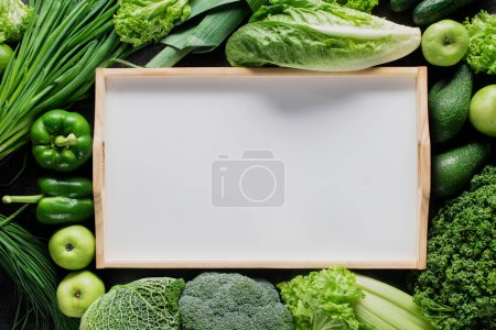 top view of blank tray between green vegetables, healthy eating concept