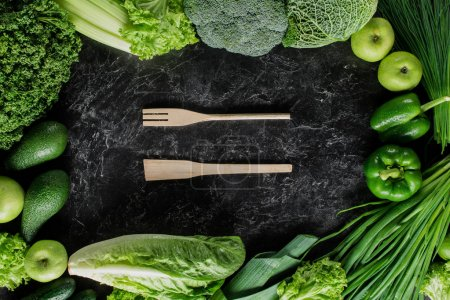 top view of wooden spatula and fork between green vegetables, healthy eating concept