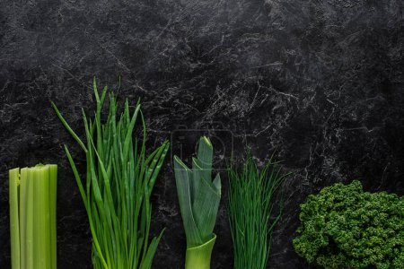 top view of green onion, leek and parsley on concrete table, healthy eating concept
