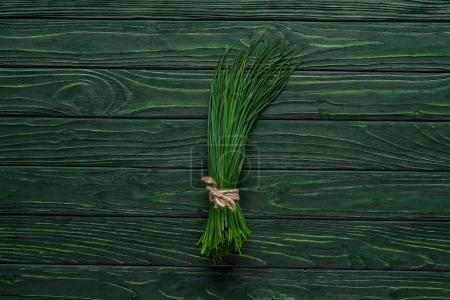 top view of bunch of chives on wooden table, healthy eating concept