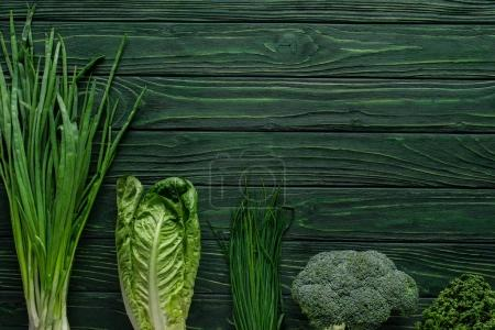 top view of green onion, broccoli and chives on wooden table, healthy eating concept