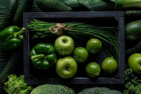 top view of green vegetables and fruits in wooden box on table, healthy eating concept