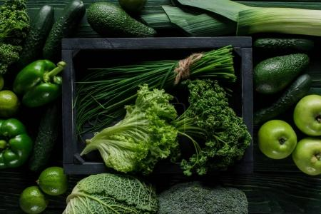 Photo for Top view of herbs in wooden box between green vegetables, healthy eating concept - Royalty Free Image
