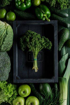 Photo pour Vue de dessus du bouquet de persil dans une boîte en bois entre les légumes verts, concept de restauration saine - image libre de droit