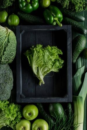 top view of salad leaves in wooden box between green vegetables, healthy eating concept