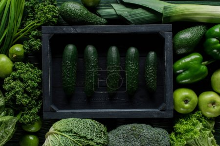 top view of cucumbers in wooden box between green vegetables, healthy eating concept