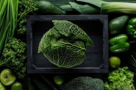 top view of green savoy cabbage in wooden box between vegetables, healthy eating concept
