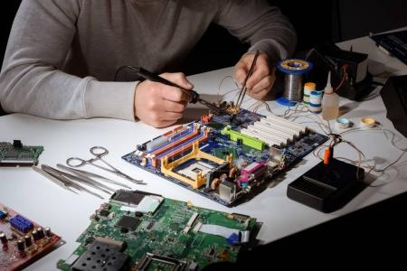 Photo for Engineer working with soldering equipment and motherboard - Royalty Free Image