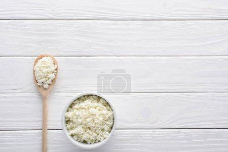 fromage cottage frais et sain dans un bol et cuillère en bois sur la table