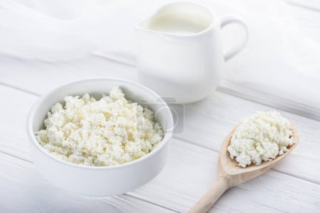 close-up view of fresh healthy cottage cheese, wooden spoon and milk in jug on wooden table