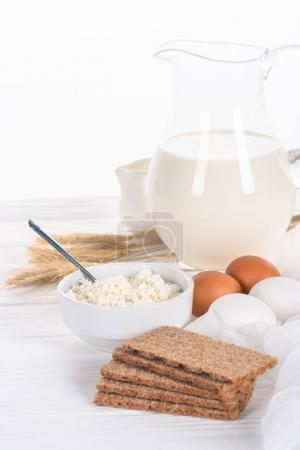 close-up view of crispy crackers, eggs, milk and cottage cheese on wooden table